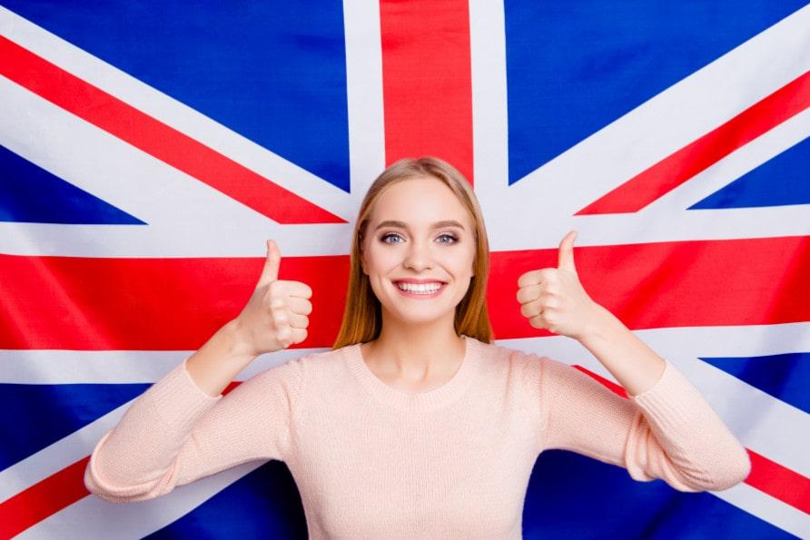 Jeune femme souriante devant le drapeau du Royaume-Uni, Union Jack
