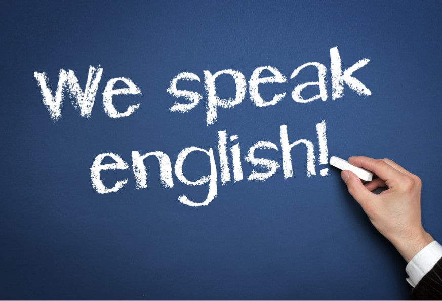 Main d'un professeur écrivant sur le tableau : We speak English